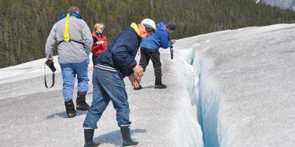 taking_a_peek_in_deep_crevasse_of_taku_glacier